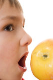 Child is a yellow apple and opens her mouth Stock Photos