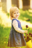 Child with yellow basket of purple tulip flowers in spring outdo Royalty Free Stock Photos