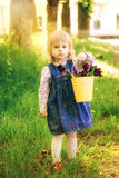 Child with yellow basket of purple tulip flowers in spring outdo Stock Image