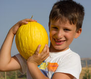 Child with a yellow melon in his hands Royalty Free Stock Photo
