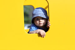 Child in yellow toy house Stock Image
