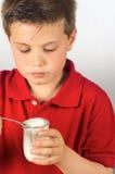 The child of yogurt 5. Photograph of a child eating yogurt over white background Stock Image