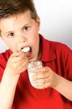 The child of yogurt 4. Photograph of a child eating yogurt over white background Royalty Free Stock Image