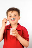 The child of yogurt 12. Photograph of a child eating yogurt over white background Stock Image