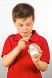 The child of yogurt 7. Photograph of a child eating yogurt over white background Royalty Free Stock Image