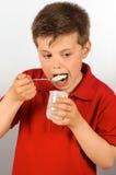 The child of yogurt 11. Photograph of a child eating yogurt over white background Stock Photography