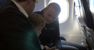 Child and young parents traveling by plane. Family of three in the plane. Little boy playing on smartphone, parents watching him, mother giving prompts stock video