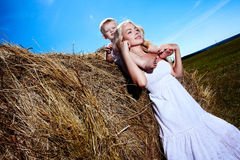 Child and young woman with flowers playing in field. Mothers day Royalty Free Stock Photo