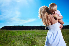 Child and young woman with flowers playing in field. Mothers day Stock Photos
