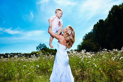 Child and young woman with flowers playing in field Royalty Free Stock Images