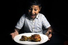 Child with yummy chicken roast. Child having a chicken drumstick to eat.