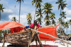 Child of zanzibar sitting on rustic fishing boat. Zanzibar, Tanzania - July 15, 2016: Black child of zanzibar, tanzania sitting on his rustic wooden fishing boat Royalty Free Stock Photo
