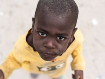 Child of zanzibar, tanzania with his head shaved. Zanzibar, Tanzania - July 15, 2016: African child of zanzibar, tanzania with his head shaved looking upward Royalty Free Stock Photography