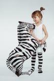 Child with zebra. Cute 4 years old kid girl posing with zebra, studio shot Stock Image