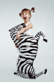 Child with zebra. Cute 4 years old kid girl posing with zebra, studio shot Royalty Free Stock Photography