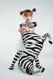 Child with zebra. Cute 4 years old kid girl posing with zebra, studio shot Royalty Free Stock Images
