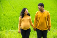 Childbearing couple hold hands and look at each other, over fresh rural country landscape. Childbearing Asian mom and dad holding hands while looking at each stock photography