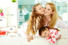 Childcare. Loving mother with her two pretty daughters having rest at home stock photography