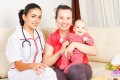 Childcare at home. Smiling mother with her happy son are sitting next to a kind nurse stock photography