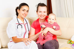 Childcare at home. Caring doctor sitting next to mother and her child at home Stock Images