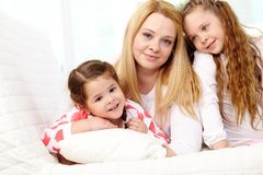 Childcare. Loving mother with her two pretty daughters having rest at home stock images