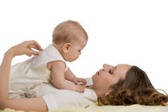 Childcare. Photo of mother plays with her baby. Childcare. Photo of young mother plays with her baby stock photography