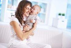 Childcare. Portrait of happy women holding her small son and expressing affection stock image