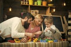 childcare pre educação escolar O pai, a mãe e o filho bonito jogam com tijolos do construtor A família na cara ocupada gasta imagem de stock