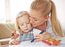Childcare. Young mother embracing her drawing daughter stock photos