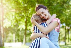 Childcare. Young smiling women embracing little girl in park while expressing love to her daughter royalty free stock image