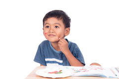 Childe asian little boy smile and thinking while doing homework Royalty Free Stock Images