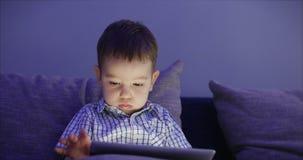 Милый ребенок развлекая с планшетом Мальчик тратя часы досуга играя мобильную игру в и задавливает яркое акции видеоматериалы