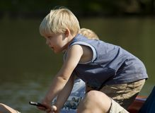 Childhood. Little boy steering a raft on the lake Royalty Free Stock Photography