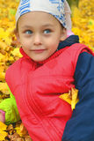 Childhood. Happy girl serenely resting on a lawn dotted with yellow leaves Royalty Free Stock Photos