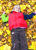 Childhood. Happy girl serenely resting on a lawn dotted with yellow leaves Stock Photos