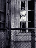 Childhood?. Sad boy in  white long-sleeved turtleneck, standing in  doorway of  old dilapidated house windows Royalty Free Stock Images