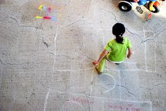 Childhood. A child playing hopscotch with a colorful toy car beside her Royalty Free Stock Photography