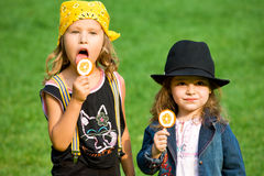 Childhood. Two little girls with lollipops on green grass Stock Photography