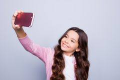 Childhood, addiction to self shots, telephone, technology, inter. Net, social nets, pre teens concept. Charming hispanic ethnicity school girl in fashionable Royalty Free Stock Image