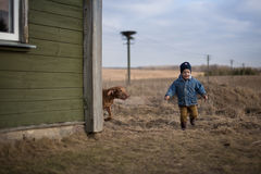 Childhood. A boy runing with a dog Stock Images