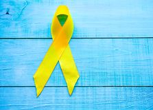 Childhood Cancer Day. Yellow Ribbon on blue background royalty free stock images