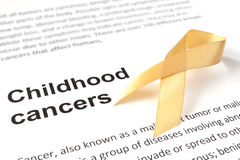 Childhood cancer. Paper with childhood cancer and gold ribbon Stock Image