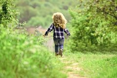 Childhood. Child run on path in spring or summer park. Boy with long blond hair on idyllic day. Childhood activity, leisure, lifestyle. Energy, growth, youth Royalty Free Stock Photo