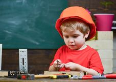 Childhood concept. Boy play as builder or repairer, work with tools. Child dreaming about future career in architecture. Or building. Kid boy in orange hard hat stock images