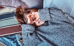Close-up portrait of a little girl in warm sweater lying on bed. stock photo