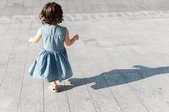 Childhood concept. Cute preschool girl is running stock image