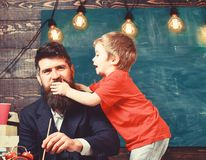 Childhood concept. Father painting while son is distracting him. Little kid holding his hand over daddy s mouth royalty free stock images