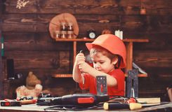 Childhood concept. Kid boy in orange hard hat or helmet, study room background. Boy play as builder or repairer, work royalty free stock photography