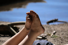 Childhood. Dirty feet of a young boy at Manzanita lake in the background with reflection. Pure childhood summer joy Royalty Free Stock Photo