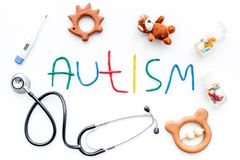 Childhood diseases. Word autism near stetoscope, pills, toys on white background top view.  Royalty Free Stock Image